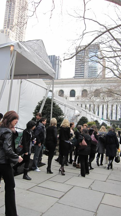 A group of Fashion Week attendees stand in front of an entrance